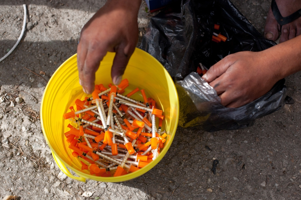 Roma bring buckets of used syringes to be replaced with clean ones. Needles are a vital commodity—they are used to prevent infection and as a form of currency in the drug world.